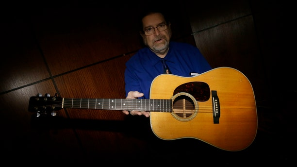 Garry Shrum, a music memorabilia specialist at Heritage Auctions, displays an acoustic guitar that belonged to Bob Dylan in Dallas.