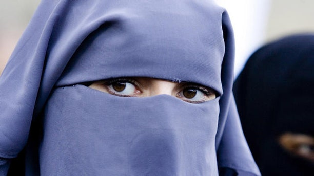"""Unidentified women wearing a niqab during a demonstration of about two dozen Muslim women outside the Dutch parliament against a proposed ban on the burqa, the head-to-toe Islamic robe, in The Hague, Netherlands, Thursday, Nov. 30, 2006. Several protesters wore long robes and veils exposing only their eyes, known as a niqab. """"We live in a free country and the government cannot tell us what to do with our religion,"""" protest organizer Ayse Bayrak told The Associated Press. Hard line Immigration Minister Rita Verdonk is drawing up legislation banning the burqa and other clothes that cover the face in public places. (AP Photo/ Fred Ernst)"""