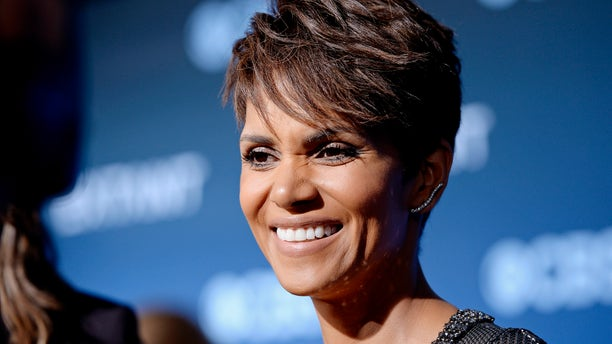 """June 16, 2014. Cast member Halle Berry of the CBS science fiction television series """"Extant,"""" smiles during an interview at the premiere of the series at the Samuel Oschin Space Shuttle Endeavour Display Pavilion in Los Angeles, California."""
