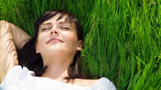 beautiful girl lying down of grass. Copy space