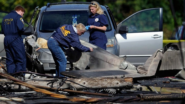 In this Oct. 12, 2016 file photo, investigators look at the remains of a small plane along Main Street in East Hartford, Conn.
