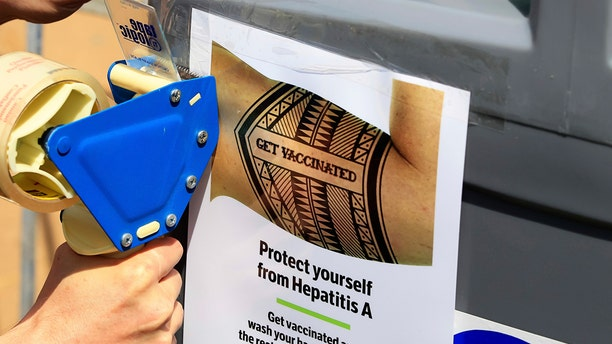 Sept. 1, 2017: In this photo, a worker tapes signage telling people to get vaccinated to protect themselves against Hepatitis A, onto sinks installed at the Neil Good Day Center on 17th Street downtown in San Diego, Calif.