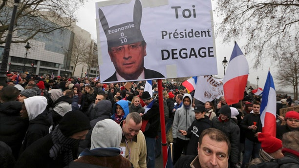 """Jan. 26, 2014: Demonstrators gather near a sign portraying French President Francois Hollande wearing donkey ears with a school grade of Zero and which reads """"You, President Resign"""" as several thousand people attend the """"Journee de la Colere"""" (Day of Anger) march in Paris."""