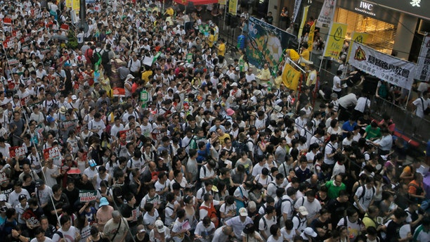 July 1, 2014: Tens of thousands of people fill in a street during a march at an annual protest in downtown Hong Kong. Hong Kong residents marched through the streets of the former British colony to push for greater democracy in a rally fueled by anger over Beijing's recent warning that it holds the ultimate authority over the southern Chinese financial center.