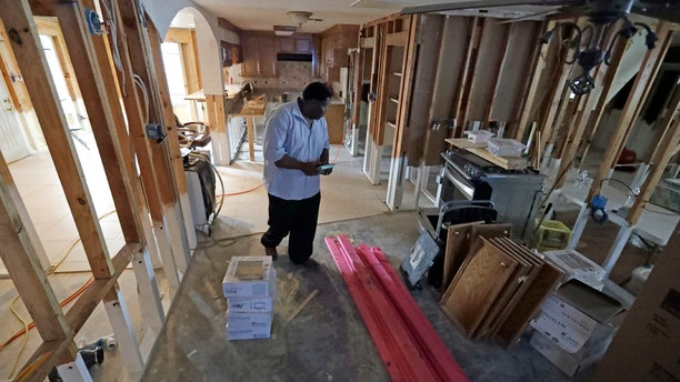 In this Nov. 17, 2017 photo, George Dorsey walks through his hurricane-damaged home in Houston. He usually hosts a large Thanksgiving dinner for family but is making other arrangements this year as he continues to recover from Hurricane Harvey.