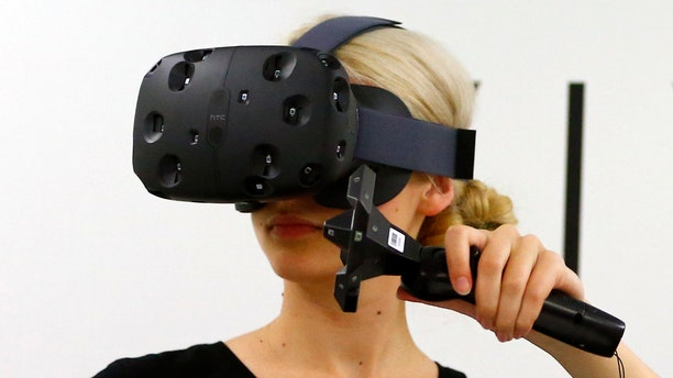 File photo - A woman checks a pair of Vive Virtual Reality goggles, produced by Taiwan's HTC, during the Gamescom 2015 fair in Cologne, Germany Aug. 5, 2015. (REUTERS/Kai Pfaffenbach)