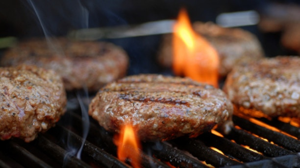 Hamburgers being flame broiled on the gas grill