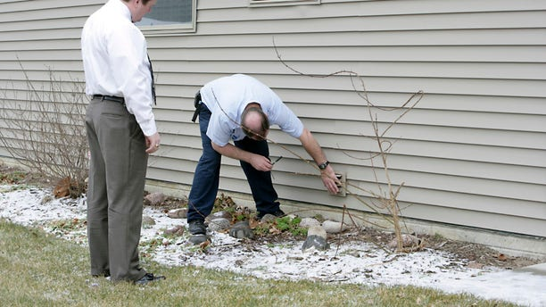 An appraiser checks out the exterior of a house.