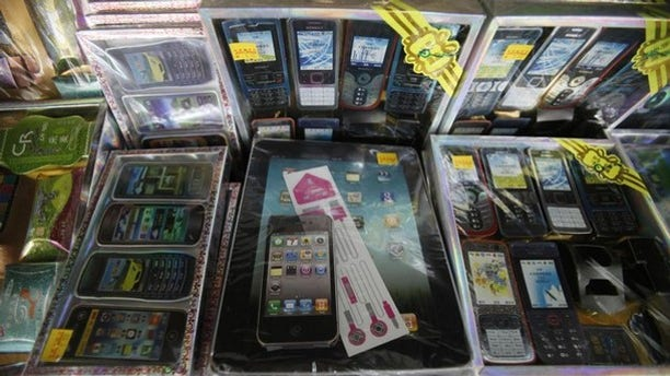 Paper replicas of first generation iPads and iPhones sit on a shelf among other electronic gadgets for sale for the Chinese Qingming festival or Ancestors Day at a prayer supplies shop in Petaling Jaya outside Kuala Lumpur.