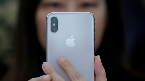 A attendee uses a new iPhone X during a presentation for the media in Beijing, China October 31, 2017. REUTERS/Thomas Peter - RC1BB5A3BB10