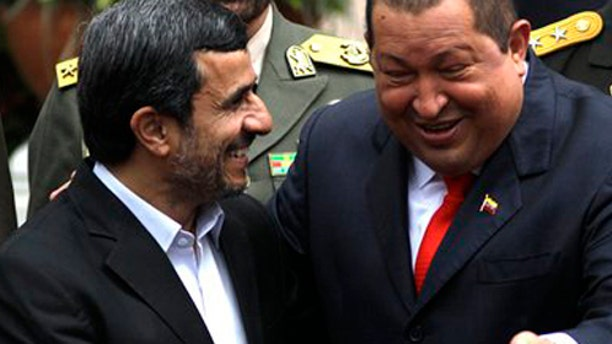 Iran's President Mahmoud Ahmadinejad, left, shares a laugh with Venezuela's President Hugo Chavez upon his arrival at Miraflores presidential palace in Caracas, Venezuela, Monday, Jan. 9, 2012. Ahmadinejad visited with Chavez as tensions rose with the U.S. over Tehran's nuclear program and a death sentence against an American man convicted of working for the CIA. Venezuela is the first leg of a four-nation tour that will also take Ahmadinejad to Nicaragua, Cuba and Ecuador. (AP Photo/Ariana Cubillos)