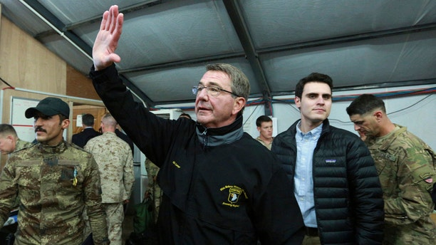 In this Dec. 11, 2016, photo, U.S. Defense Secretary Ash Carter waves to a group of Iraqi and U.S. soldiers during his visit to the Qayara air base, south of Mosul, Iraq.