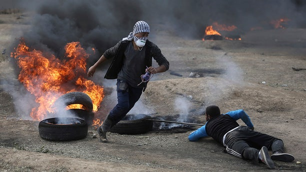 May 14, 2018: Palestinian protesters burn tires during a protest on the Gaza Strip's border with Israel.