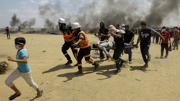 May 14, 2018: Palestinian medics and protesters evacuate a wounded man during a protest at the Gaza Strip's border with Israel, east of Khan Younis, Gaza Strip.