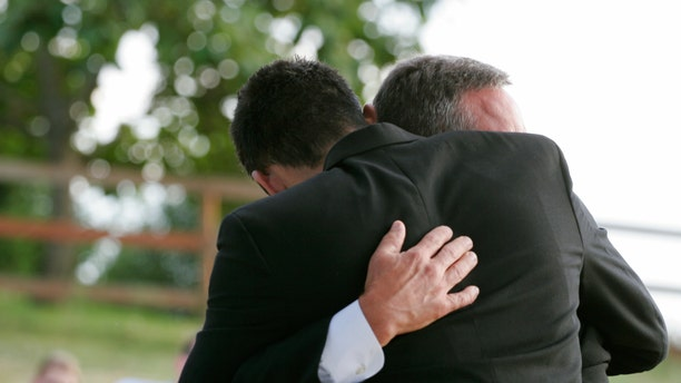 Two men hug each other.  Horizontal with copy space.