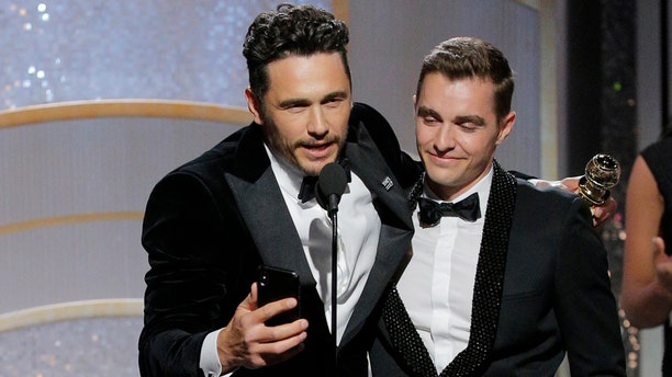 James Franco accepts the award for Best Actor in a Comedy or Musical at the 75th annual Golden Globes with brother Dave Franco.