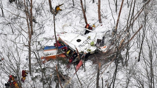Rescuers work near the helicopter crashed in mountains in Nagano prefecture, central Japan Sunday, March 5, 2017. The rescue helicopter carrying nine people has crashed in snow-coved mountains during a training flight.