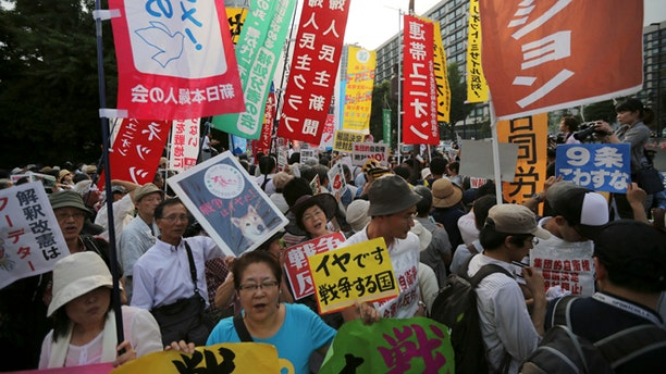July 1, 2014: Protesters shout slogans outside the Japanese Prime Minister Shinzo Abe's official residence in Tokyo as Abe's Cabinet approved reinterpreting the constitution on military affairs.