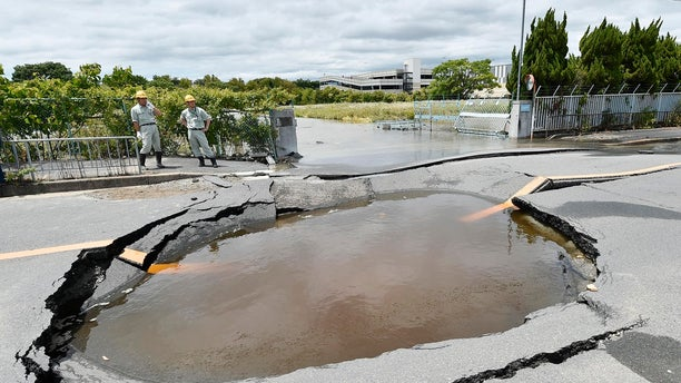 A collapsed road is filled with water after water pipes broke following an earthquake in Takatsuki city, Osaka, western Japan, June 18, 2018.