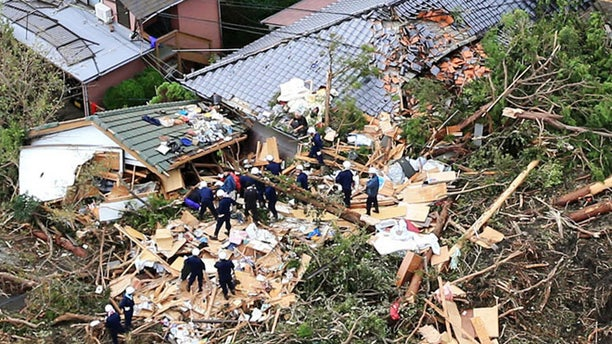 Oct. 16, 2013: Rescue workers look for survivors as they stand on the rubble of a house buried by mudslides after a powerful typhoon hit Oshima on Izu Oshima island, about 75 miles south of Tokyo Wednesday morning.
