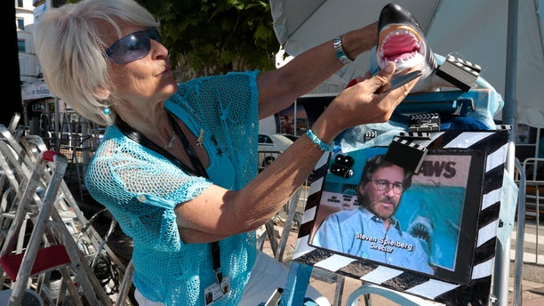 Cinema fan Martine Santoro adjusts a model of a shark as featured in the movie 'Jaws' by director and president of the 66th Cannes Film Festival, Steven Spielberg, on her step ladder in front of the Festival Palace during the Festival in Cannes May 19, 2013.      REUTERS/Eric Gaillard (FRANCE  - Tags: ENTERTAINMENT)   - RTXZSEY