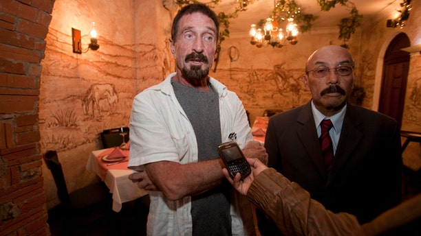 Dec. 4, 2012: Software company founder John McAfee, left, accompanied by his lawyer Telesforo Guerra, right, answers questions during an interview at a local restaurant in Guatemala City.