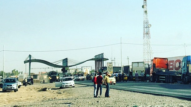 Trucks line up at a checkpoint to enter Kirkuk, following Friday's attack.