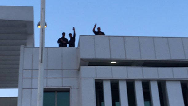 Kurdish forces keep watch atop buildings following the sleeper cell attack.