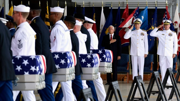 Vice President Mike Pence, Commander of U.S. Indo-Pacific Command Adm. Phil Davidson, center, and Rear Adm. Jon Kreitz, deputy director of the POW/MIA Accounting Agency, watch as military members carry transfer cases from a C-17 at a ceremony marking the arrival of the remains believed to be of American service members who fell in the Korean War at Joint Base Pearl Harbor-Hickam, Hawaii, Wednesday, Aug. 1, 2018. North Korea handed over the remains last week. (AP Photo/Susan Walsh)