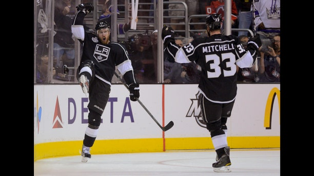 Los Angeles Kings center Jeff Carter (77) and Los Angeles Kings defenseman Willie Mitchell (33) react after Carter's third period goal against the New Jersey Devils during Game 3 of the Stanley Cup Finals, Monday, June 4, 2012, in Los Angeles. The Kings won 4-0. (AP Photo/Mark J. Terrill)