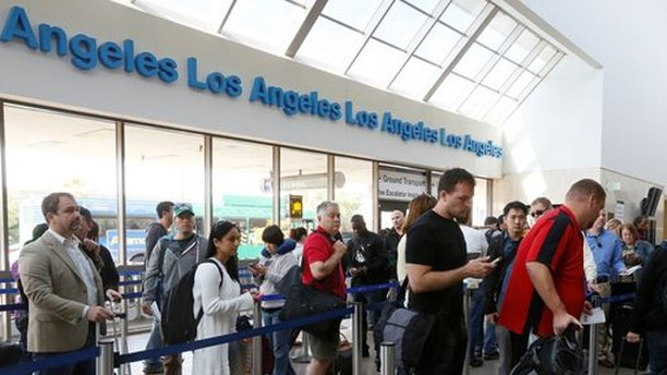 Travelers stand in line at Los Angeles International Airport on Monday, a tough start to the week for many air travelers because of flight delays.
