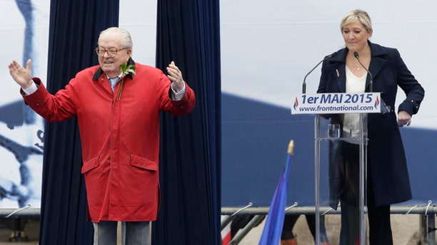 France's far-right National Front political party leader Marine Le Pen (R) watches as her father Jean-Marie Le Pen, party founder and honorary president, reacts on the podium at their traditional May Day tribute to Joan of Arc in Paris, France.