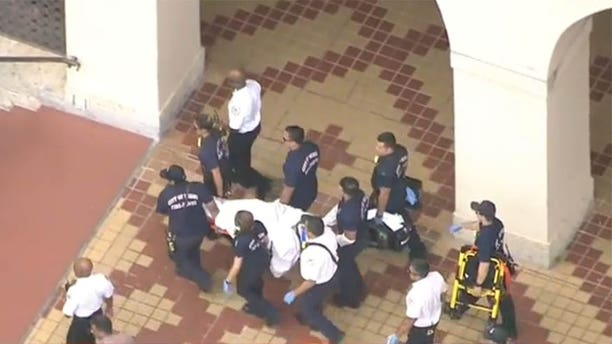 May 3, 2017: An injured suspect is carried away by responders after shots were fired inside the Miami-Dade Library.