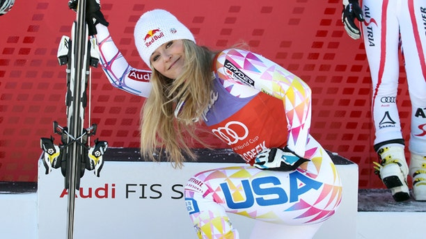 In this Dec. 7, 2011 file photo, Lindsey Vonn kneels down in front of the podium after winning the women's World Cup Super G  ski competition in Beaver Creek, Colo.