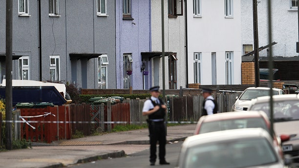 Police officers stand behind cordon tape near a property that was searched after an explosion on a London Underground train, in Sunbury-on-Thames, Britain, September 16, 2017. REUTERS/Peter Nicholls - RC198DFC0FE0