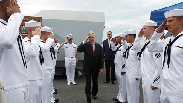 U.S. Secretary of the Navy Ray Mabus salutes servicemen as he leaves the USS Freedom littoral combat ship after his visit, at Changi Naval Base in Singapore May 11, 2013.