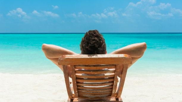 Man relaxing on beach, ocean view, Maldives island