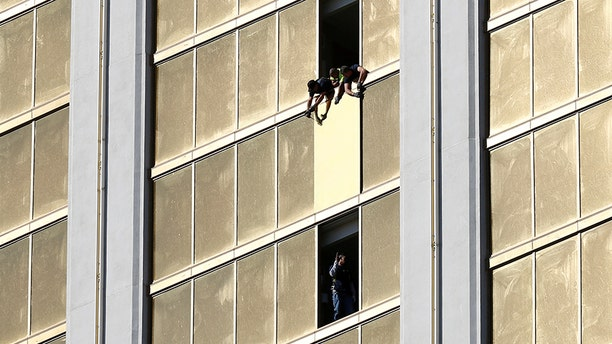 Oct. 6, 2017: Workers board up a broken window at the Mandalay Bay hotel, where shooter Stephen Paddock conducted his mass shooting along the Las Vegas Strip.