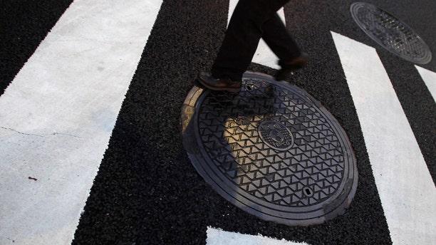 A pedestrian passes a manhole.