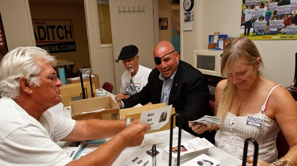 """Sept. 17, 2012: In this photo, Nick Popaditch, center, candidate for 53rd congressional district and a United States Marine veteran who fought in Iraq and sustained serious injuries, works with his campaign volunteers in his office in La Mesa, Calif. """"I was looking at my government and I wasn't happy with it,"""" says the ex-gunnery sergeant. """"So rather than complain, I decided to run myself. I thought I could do a better job, and I still feel that way."""""""