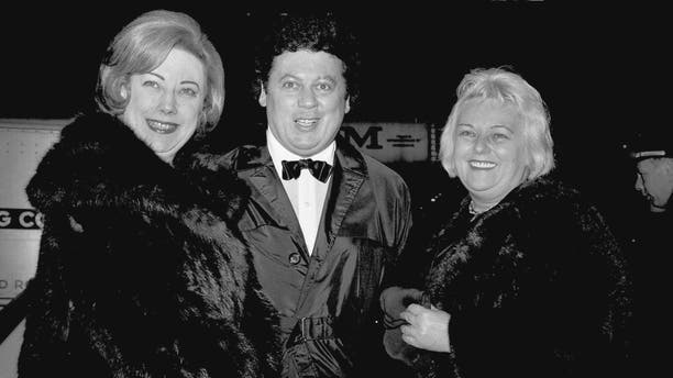 """FILE - In this March 16, 1965, file photo, comedian Marty Allen, center, arrives for the premiere of """"The Train"""" with his wife Frenchie, right, and Rosemary Wilson, wife of columnist Earl Wilson, in New York. Allen's spokeswoman Candi Cazau says he died Monday, Feb. 12, 2018, of complications from pneumonia. His wife and performing partner Karon Kate Blackwell was by his side. He was 95. (AP Photo/John Lent, File)"""
