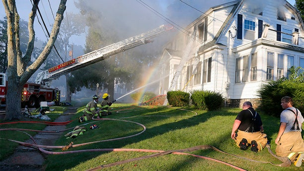 Firefighters battle a house fire in North Andover on Thursday.