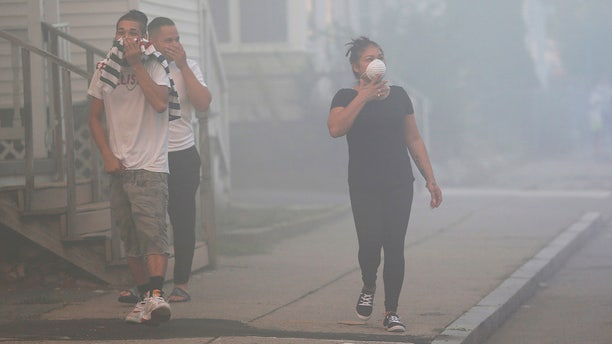 People cover their faces to protect themselves from heavy smoke from a fire on Bowdoin Street in Lawrence, Mass.