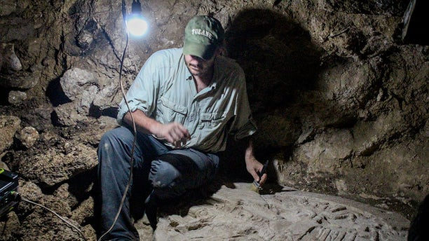 Tulane archaeologist Marcello A. Canuto sits beside the altar he and his team discovered in the jungles of northern Guatemala. (Photo courtesy of the National Museum of Archaeology and Ethnology in Guatemala City)