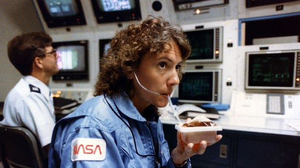 Christa McAuliffe, seen in 1985 taking a sip from a space-packaged drink prior to her ill-fated flight on space shuttle Challenger, was to teach from orbit. Some of her lessons, including working with liquids in zero-G, will now be completed on the International Space Station.