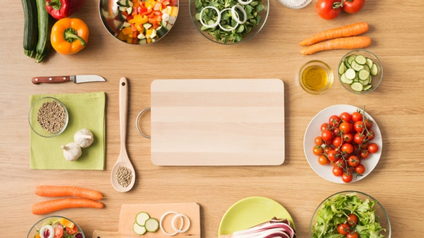 Creative vegetarian cooking at home concept with fresh healthy vegetables chopped, salads and kitchen wooden utensils, top view with copy space