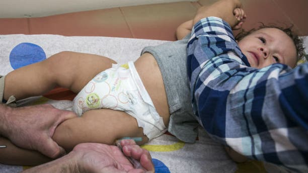 In this Thursday, Jan. 29, 2015, photo, pediatrician Charles Goodman vaccinates 1-year-old Cameron Fierro with the measles-mumps-rubella vaccine, or MMR vaccine, at his practice in Northridge, Calif. (AP Photo/Damian Dovarganes)
