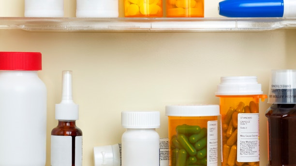 Several containers of over the counter and prescription medications on the shelves of a 1960's medicine cabinet.