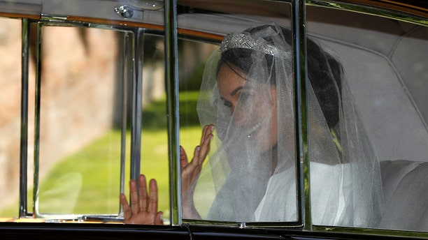 Meghan Markle waves from the car as she travels to her wedding at St. George's Chapel at Windsor Castle.