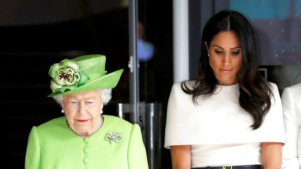 Britain's Queen Elizabeth and Meghan, Duchess of Sussex observe a moment of silence in memory of the victims of the Grenfell Tower fire during their visit Storyhouse Chester